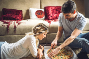 picture of young couple in home enjoying pizza delivery